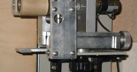 <b> Tažný strojek</b>:  Pomocí tažného strojku se vytahuje vlákno z hladiny roztaveného skla v Pt kelímku. Pro požadovaný průměr taženého vlákna musíte nastavit teplu, otáčky a vzdálenost strojku nad píckou.